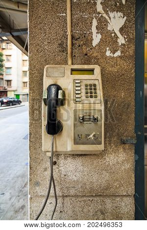 Abandon public card telephone installed on the pole of building for public use in Guangzhou China