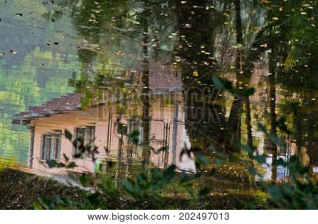 Reflection in a river as an aquarell of a village life at sunset, near Valjevo, Serbia