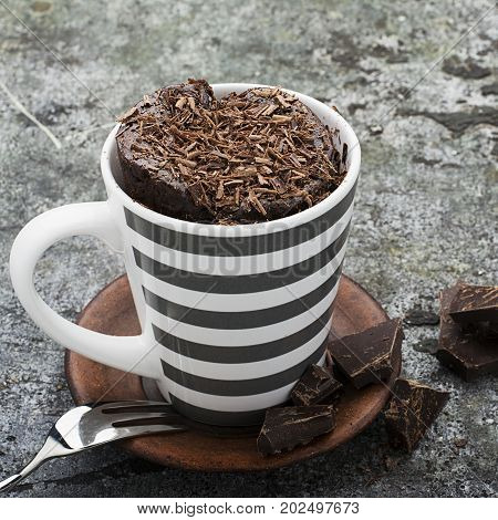 Homemade chocolate aromatic mug cupcake in a stylish gray striped mug on a gray stone background with bits of bitter chocolate. Selective focus