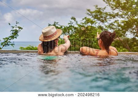 Back view on two girl in pool. Gitl spent time in vacation club