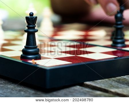 Queen on the chessboard, Chess figure, Black queen. Playing chess on the street.