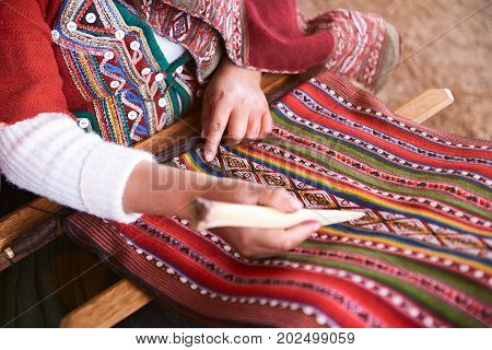 Hands of peruvian woman making alpaca wool close-up. Manufacture of wool material in Peru