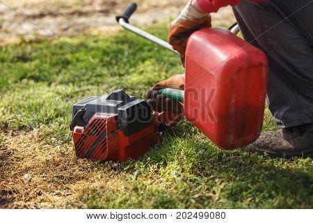 Refuelling petrol on trimmer machine in yard