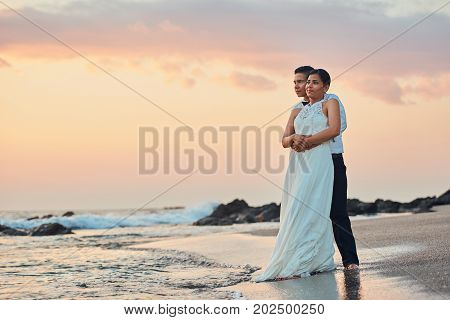 Just married happy young couple stand on ocean beach sunset colorful background