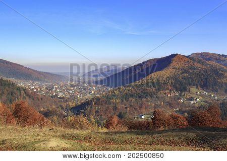 Autumn landscape in Carpathian lowlands with colorful forests and a village in a valley