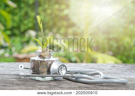 Stethoscope on bottle coin and plant on wooden background. Concept of financial planning for health care.