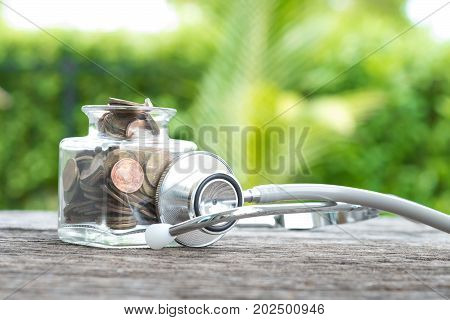 Coin bottle stethoscope on wooden. concept of financial planning for health care.