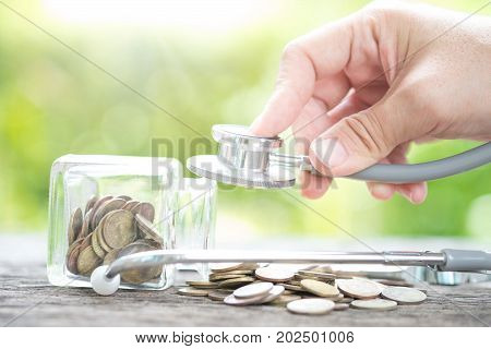 Stethoscope on bottle and coin on wooden background. Concept for finance health check or cost of business financial analysis audit or accounting.