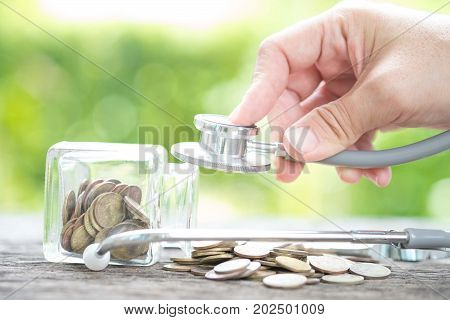Stethoscope on bottle and coin on wooden background Determined image for solution or key to protect and check money with out risk concept.