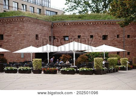 MAINZ, GERMANY - AUGUST 21: Visitors of a café of the Hyatt Regency Hotel sit under umbrellas at Fort Malakoff on August 21, 2017 in Mainz.