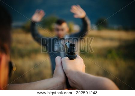 The Policeman Holds A Pointed Weapon And Arrests A Criminal, A Thief, A Drug Dealer, Surrendered, An