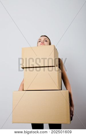 Woman holding a pile of packaged parcels. Woman doing something. Carton.