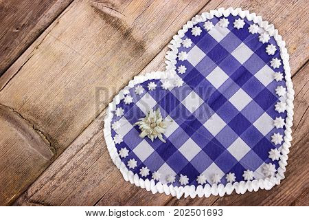 A blue checkered heart with edelweiss on a wooden background