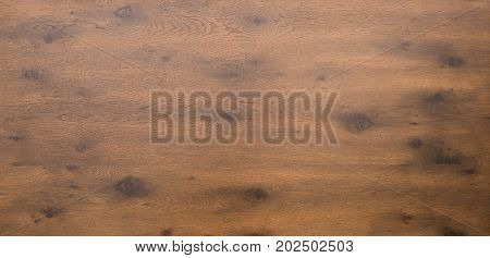 Aerial or above shot of a dark wooden table top with timber and knots