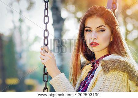 Beautiful teenage girl in park in autumn