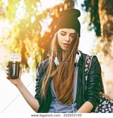 Teenage girl in autumn in park holding takeaway coffee