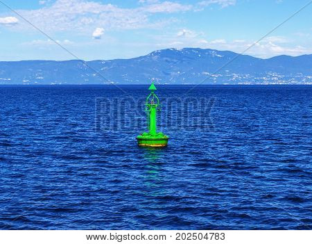 A green channel marker buoy in the water.