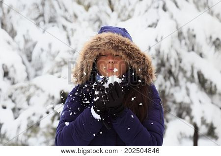 Beautiful Girl At Winter Blowing Snow In Frosty Winter Park. Flying Snowflakes. Sunny Day. Beauty Yo