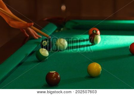 Playing man by cue in billiard pool close-up balls bar.