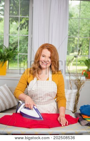 Smiling mid aged woman ironing clothes. Typical day of female doing housework.