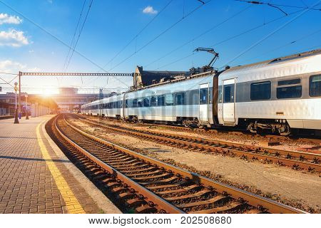 Beautiful passenger train at the railway station at sunset. Industrial view with modern intercity train, railroad, railway platform and blue sky in the evening. Railway tourism and transportation