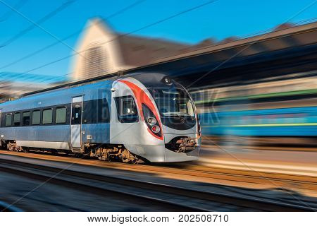 High speed train in motion at the railway station at sunset in Europe. Modern intercity train on the railway platform with motion blur effect. Industrial scene with moving passenger train on railroad