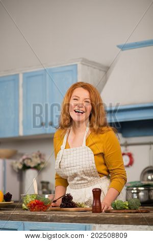 Happy mid aged housewife cooking in kitchen at home. Woman smiling cooking vegetables.