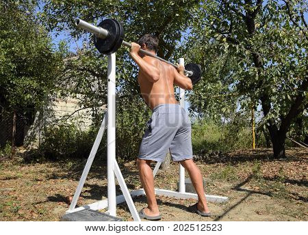 Man Takes A Bar To Perform Squats. Exercises In Bodybuilding. Sport In The Backyard.