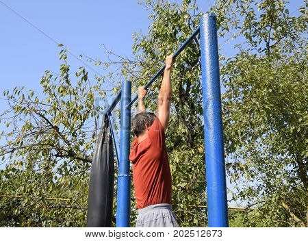 The Man Pulls Himself Up On The Bar. Playing Sports In The Fresh Air. Homemade Horizontal Bar In The