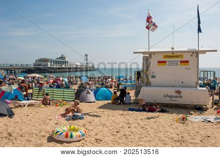 Bournemouth UK - August 28 2017: Busy beach in a hot summer day with a Pier Amusements in the background and Lifeguard in the foreground