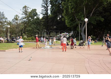 SYDNEY,NSW,AUSTRALIA-NOVEMBER 20,2016: Street busker and children playing with tri-string bubble wand and bubbles in Hyde Park in Sydney, Australia.