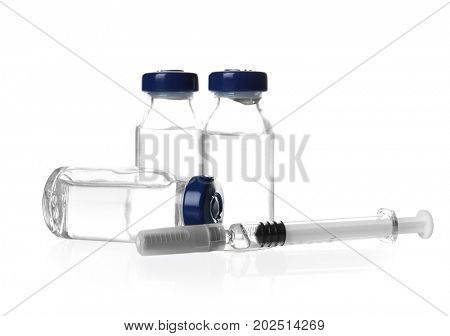Ampules with vaccine and syringe on white background