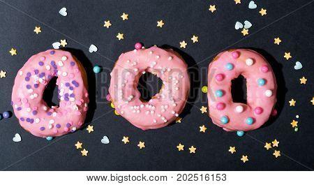 Colorful glazed donuts on a chalky black background