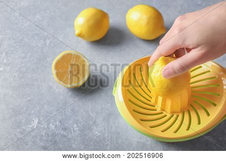 Man's hand juicing lemon with plastic squeezer on grey background