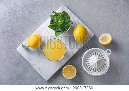 Composition with lemons, glass of juice, mint and plastic squeezer on grey background