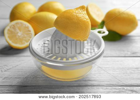 Composition with lemons and plastic squeezer on wooden table