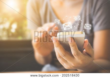 Asian woman hand using mobile phone with e-mail application Concept email and newsletter