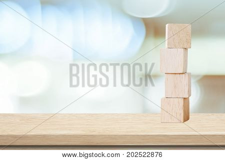 Four wooden cubes on table over blur abtract bokeh light background