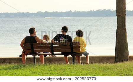 Jacksonville, Florida - July 15, 2013: Father and three children sitting on the bench near the lake in Jacksonville, Florida