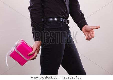 Man Hiding Pink Gift Box With Ribbon Behind Back