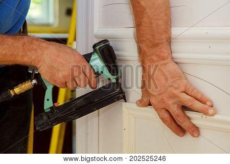 Home Improvement Carpenter brad using nail gun to Moulding