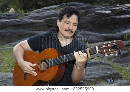 A Hispanic man sits in park and plays an acoustic nylon string guitar.