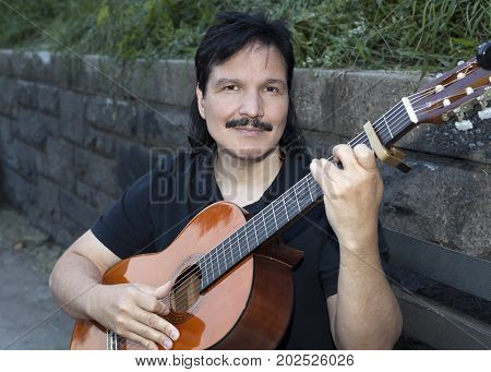 Hispanic man sitting on bench with classical guitar.