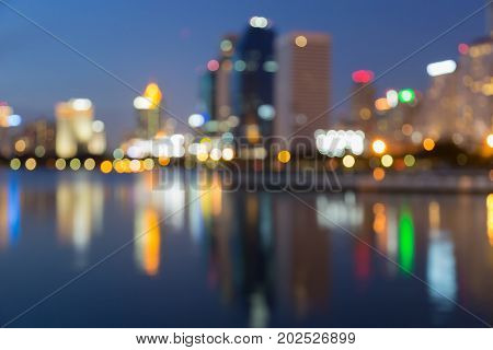 Blurred bokeh reflection light office building at twilight abstract background