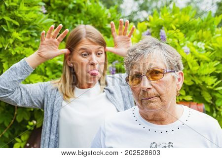 Young grimacing female with angry grandmother outdoor in the garden