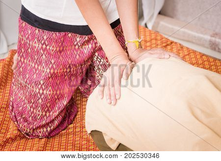 Massage therapist is massaging a women hip and back