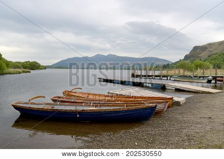 Rowing boats on shore of Derwentwater, English Lake District