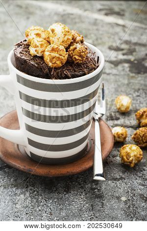 Chocolate aromatic mug cake with caramel appetizing popcorn for autumn cozy warm tea drinking on a gray stone background in a stylish gray striped mug. Selective focus