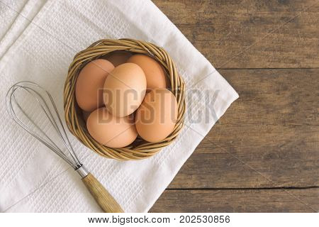 Fresh eggs in old wood basket put on white napkin. Prepare fresh chicken eggs for cooking or bakery on wood rustic wood table. Top view or flat lay of eggs with copy space for background or wallpaper. Fresh eggs for baking.