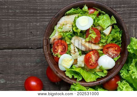 Fresh salad caesar with chicken quail eggs tomatoes and lettuce in a bowl on rustic wooden background with copy space. top view